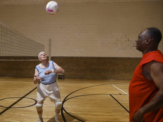 Robert Luscombe, left, practices hitting the ball between sets with friend Rodney Wilson of Lansing.  Luscombe still works. He will turn 85 in August.  He has been playing volleyball at Foster Community Center with the Lansing Parks and Recreation league every Tuesday for more than 20 years.