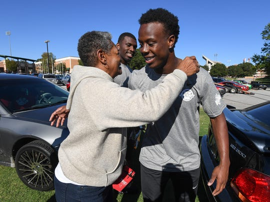 Crystal McLendon hugs Clemson running back Travis Etienne after he and running back Tavien Feaster, back, helped load food into her car on Tuesday, October 17, 2017. The food was boxed and given to people as part of the Clemson football team's community service project benefiting the Golden Harvest Food Bank.