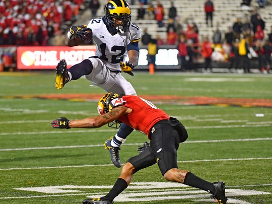 Michigan running back Chris Evans (12) leaps over Maryland
