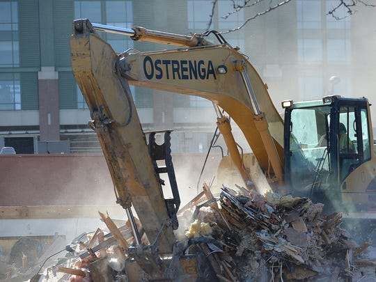 An excavator brings down the Road Star Inn on Tuesday in the shadow of Lambeau Field.