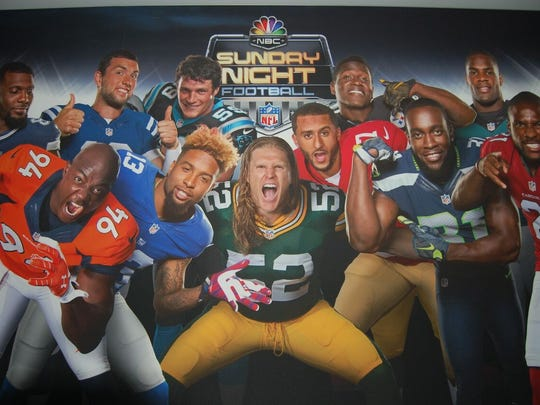 "A life-size photobomb wall featuring NFL players, including Green Bay Packers linebacker Clay Matthews, center, is among the fan activities on the ""Sunday Night Football"" bus."