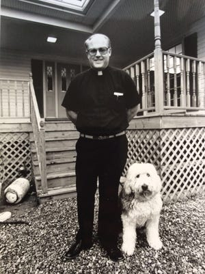 The Rev. Jonathan Wehrle poses with his sheepdog Thumper outside his Okemos home in February 1989 shortly after its construction. Wehrle was the general contractor on the house and did much of the work himself.