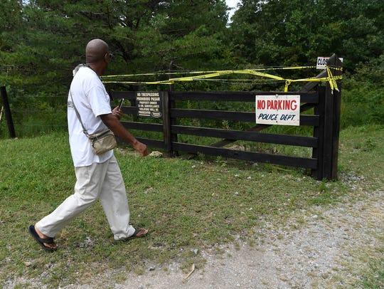 Robert Walker walks past a fortified fence Friday,