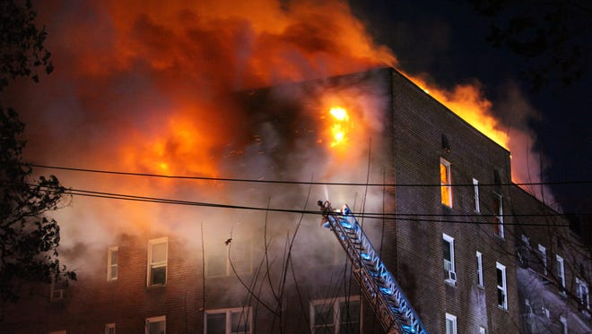 Fire shoots out of the top floor of this apartment building at 1 Hawley Terrace in Yonkers, as Yonkers firefighters battle a general alarm fire, March 15, 2017.