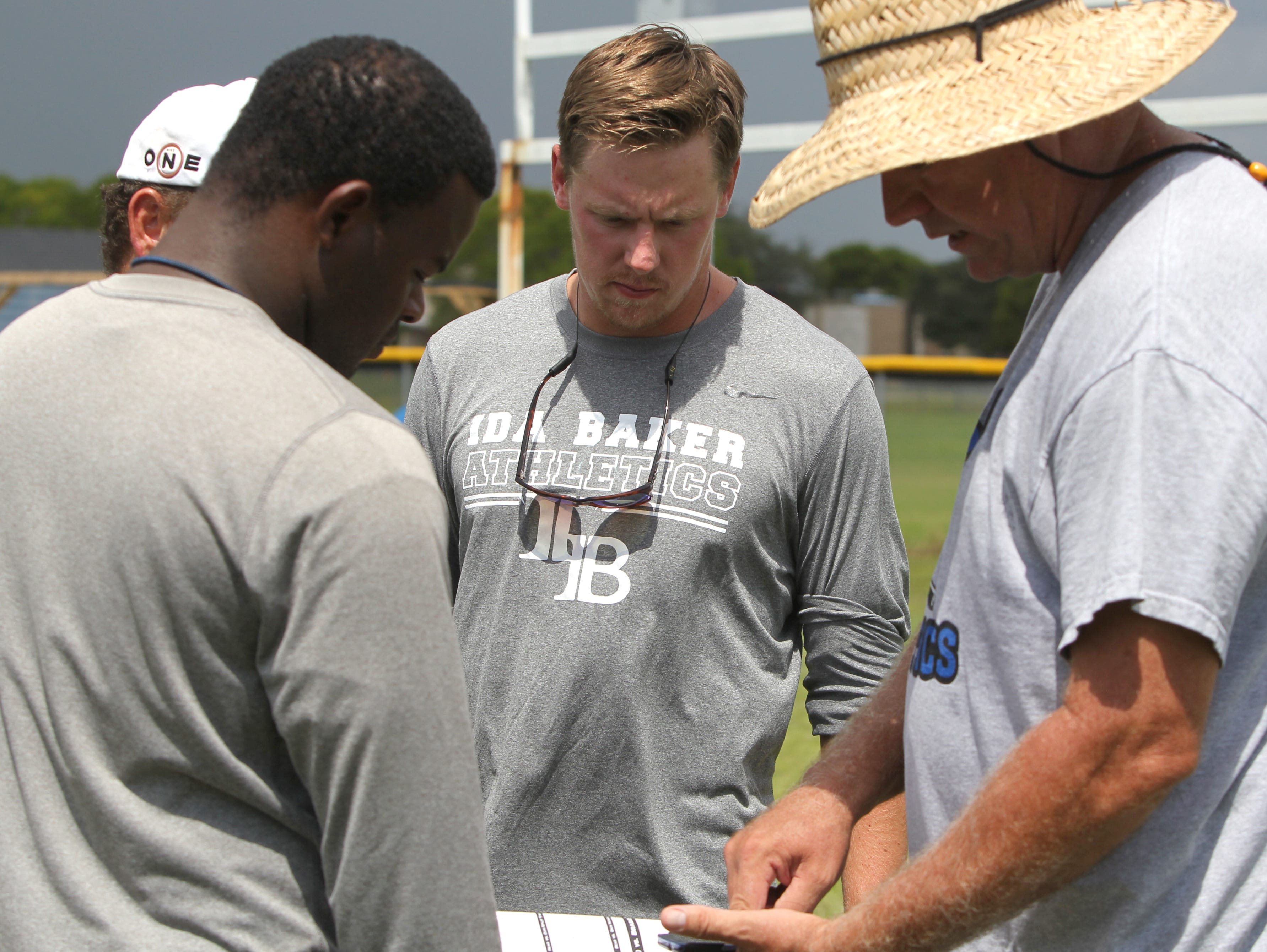 Cullen O'Brien, center, plans afternoon practice with other coaches during practice at Ida S. Baker High School in Cape Coral Wednesday.