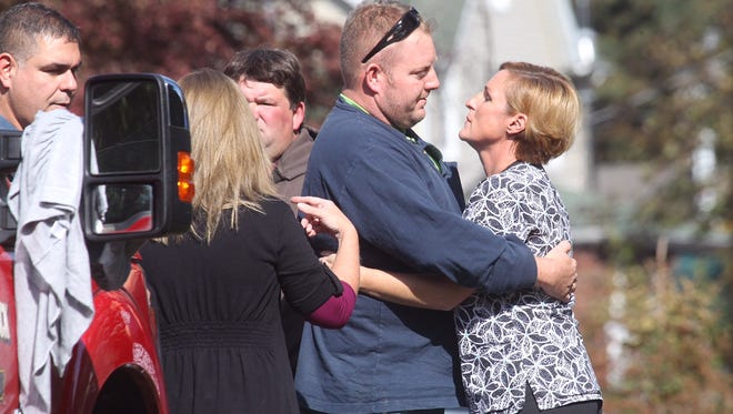 People console one another near the site where two people were found dead on Adam Court In Sloatsburg.