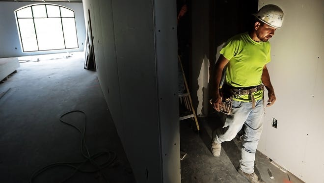 Jorge Loa works on the drywall in apartments at the new Thornwood mixed-use development on Germantown Road. Construction at the 17-acre, $100 million development is expected to continue for another18 months.