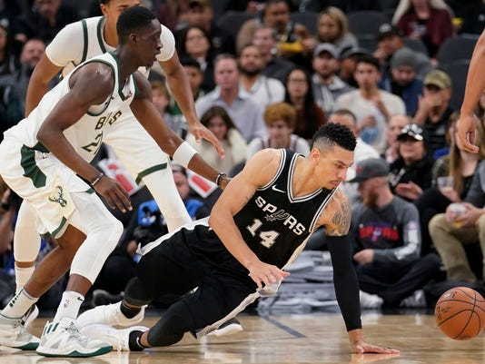 San Antonio Spurs guard Danny Green (14) falls as he chases the ball next to Milwaukee Bucks guard Tony Snell during the first half of an NBA basketball game, Friday, Nov. 10, 2017, in San Antonio. (AP Photo/Darren Abate)