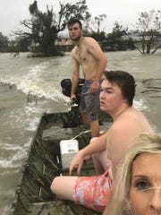Scout Morris, back, rides around Everglades City with his cousin Connor Weeks and his mother, Pastor Lynnette Morris, in the aftermath of Hurricane Irma. Morris and his family took their boat around town to help neighbors arrive safely to shelter.