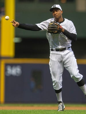Jonathan Schoop, in his first start at shortstop this season, makes a throw to first after charging a chopper against the Rockies in the fourth inning during his Miller Park debut as a Brewer on Friday night.