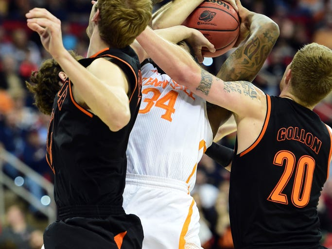 Mercer's Anthony White Jr. (15) and Jakob Gollon (20) fight for a rebound with Tennessee forward Jeronne Maymon (34) during the first half. UT won 83-63.