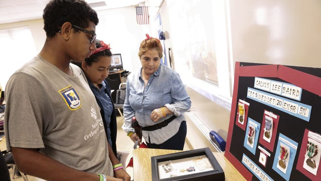 Teacher Vickie Hebert, right, looks at World War II memorabilia with students during a 1940s symposium at Early College Academy in November. ECA is one of several local schools to earn a bronze medal from U.S. News and World Report.