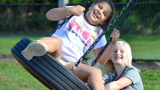 Nicole Wiley (right) pushes her best friend, Aubrianna Asher, on the tire swing.