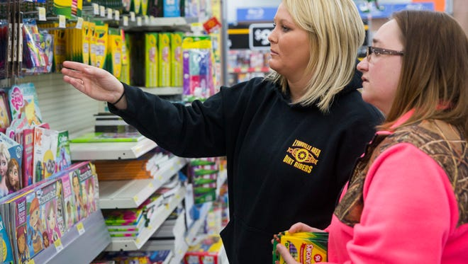 Leah Bond, left, and Nicole Lyell decide on packages of coloring utensils for a family with 4 kids that the Tulip Tree Family Health Care shop for during the Christmas season on Sunday afternoon at Walmart.