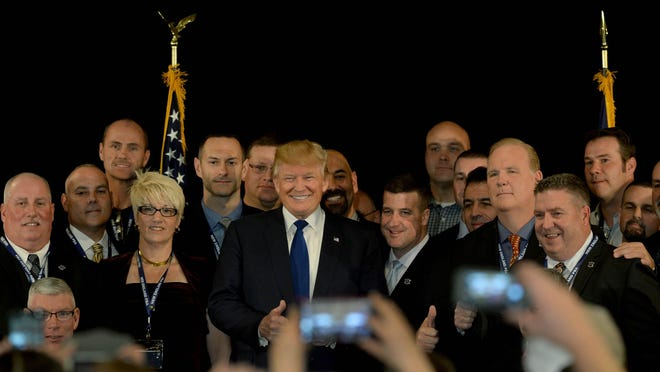 PORTSMOUTH, NH - DECEMBER 10: Republican presidential candidate Donald Trump stands with law enforcement officers after receiving the endorsement of the New England Police Benevolent Association at the Sheraton Portsmouth Harborside Hotel December 10, 2015 in Portsmouth, New Hampshire. Trump has made controversial remarks regarding Muslims recently, saying he would implement a ban on all Muslims entering the United States. (Photo by Darren McCollester/Getty Images) *** BESTPIX ***