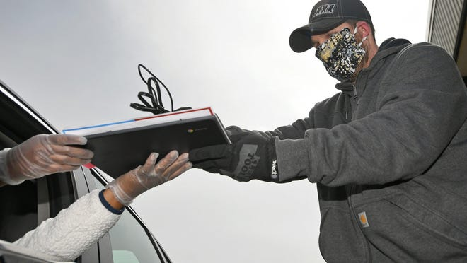 Dan Gibbons, an information technician for the Erie School District, hands a laptop and charger cord to a driver on April 14 in a parking lot at Erie High School. The district is buying computers for every student in response to the COVID-19 crisis, a move that could also eliminate snow days in the district.
