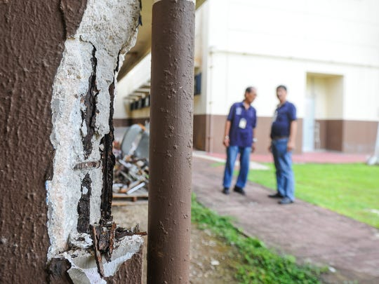 In this July 2016 file photo, maintenance workers look at crumbling concrete on a column at the Z-wing of the Guam Memorial Hospital in Tamuning. Other areas, including the building's second-floor interior and on the front exterior overhang, concrete can be seen crumbling away from the structure. Employees working in the affected section have been moved to other areas of the hospital.