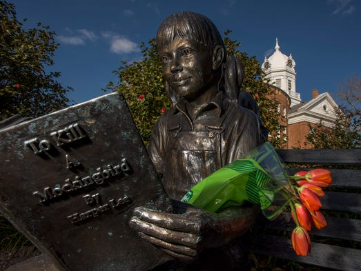 Someone placed tulips on a statue of a child reading