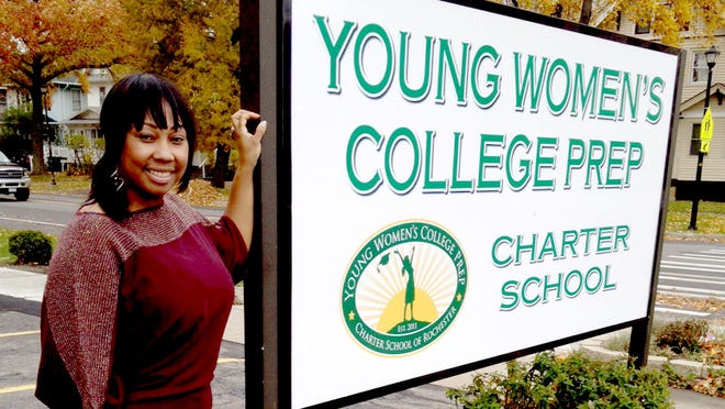 Lashunda Leslie-Smith poses in front of Young Women's College Prep Charter School.