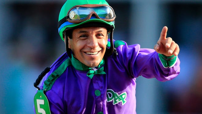 Jockey Victor Espinoza celebrates atop of California Chrome after crossing the finish line to win the 140th running of the Kentucky Derby on May 3, 2014.
