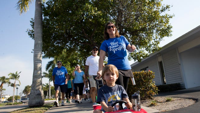 Kristin Schon smiles as she pushes her son Zeke Schon, 3, during the Blue Zones Project of Southwest Florida mile-long community walk from Cambier Park in downtown Naples to the Garden of Hope and Courage at the NCH campus in honor of National Walking Day Wednesday, April 5, 2017.
