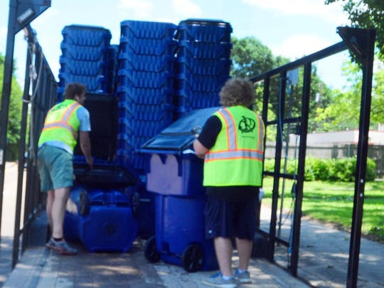 Workers from Progressive Waste Solutions drop off plastic garbage containers along Union Street.