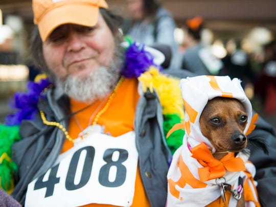 Jim Sanders holds his dog Hadassah while waiting for the Young-Williams Animal Center's 10th annual Mardi Growl parade to begin in 2017.