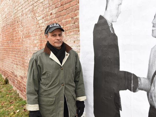 """Franc Palaia, an artist and muralist from Rhinebeck, pictured next to one of his installments in a series of a murals called """"Community Portraits."""""""