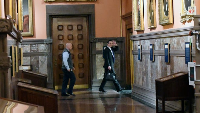 New York Gov. Andrew Cuomo, right, walks through the Hall of Governors as he arrives for work at the state Capitol Friday, March 30, 2018, in Albany, N.Y.