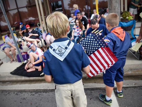 Scouts pass out programs and flags Wednesday before