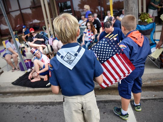 Scouts pass out programs and flags Wednesday before the start of the St. Joseph Lions 2018 Fourth of July Parade.