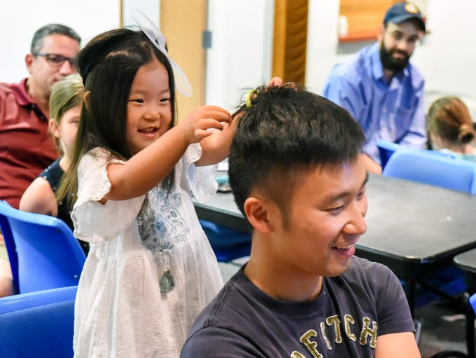 Hael Cho, 2, takes a turn styling the hair of her father,