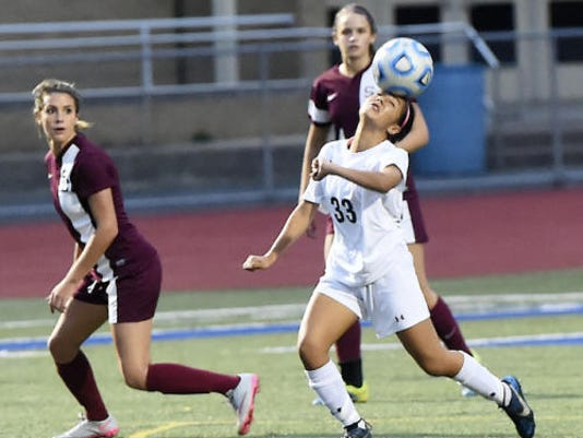 Chambersburg's Jasmine Lemus (33) heads a ball while Sarah Scott of State College looks on during their game Tuesday at Trojan Stadium. The Little Lions took a 2-1 win.