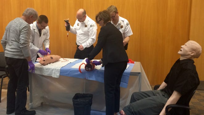 West Des Moines Deputy City Manager Jamie Letzring, center, learns how to apply a tourniquet to a bleeding limb as part of a Stop the Bleed initiative.