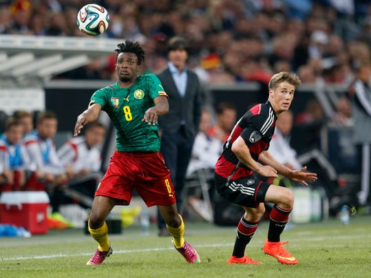 Germany's Erik Durm, right, and Cameroon's Benjamin Moukandjo challenge for the ball during a soccer friendly match between Germany and Cameroon in Moenchengladbach, Germany, Sunday, June 1, 2014. (AP Photo/Michael Probst)