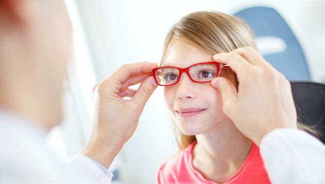 Little brown eyed  girl visiting optician.She's having appointment for testing new glasses.Middle aged male optician is gently adjusting new frame and glasses on girl's face.