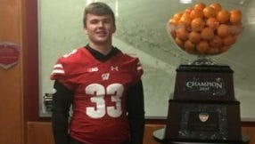 Southern Door football player Derik LeCaptain poses in the Wisconsin Badgers football offices with the Orange Bowl trophy.