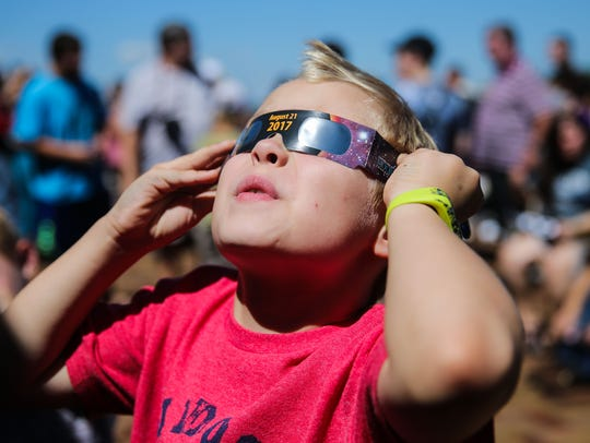 Walker Carroll, 7, looks through eclipse glasses at