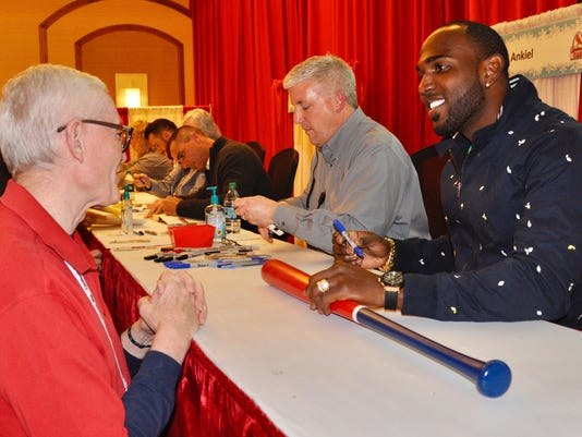 "St. Louis Cardinals' Marcell Ozuna, right, talks with a fan while giving autographs during the team's annual ""Winter Warm-Up"" on Sunday, Jan. 14, 2018, in St. Louis. Ozuna was traded to the Cardinals from the Miami Marlins last month, and the All-Star outfielder is expected to have an immediate impact in the St. Louis lineup. (AP Photo/Kurt Voigt)"
