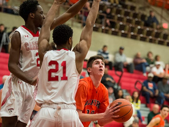 Palmyra's Isaac Blatt looks for a way to the hoop against Archbishop Carroll's Khari Williams and Archbishop Carroll's Jesse McPherson as Palmyra fell to Archbishop Carroll 78-41 in the second round of the PIAA 5A basketball tournament at Reading High School on Thursday, March 16, 2017.