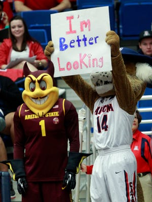 Arizona's mascot Wilbur holds a sign behind ASU mascot Sparky during a 2014 basketball game at McKale Center in Tucson.
