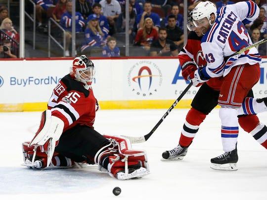 New Jersey Devils goalie Cory Schneider (35) kicks the puck away as teammate defenseman John Moore battles Rangers center Daniel Catenacci (43) during the first period of a preseason NHL hockey game in Newark on Saturday, Sept. 23, 2017.