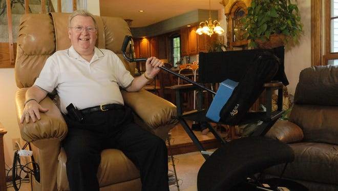 """Gary Beyer sits in his hydraulic sleep chair which can lift him to almost a standing position. He is holding onto an EZ-Step which allows him to climb stairs, an Aquila Elevated Seat pad that he takes to restaurants, and a pneumatic lift for chars he sits in to get out of. Beyer is one of 12 people in Wisconsin who has Inclusion Body Myositis, a disease that is untreatable and incurable which attacks the muscles. He has written his second book, """"I Promise I'll Pay Attention."""""""
