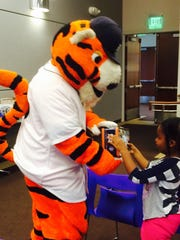 Four-year-old Amanda Shorter of Westland won a Detroit Tigers-themed prize from mascot PAWS at the Farmington Community Library.