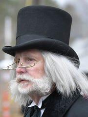 Ebenezer Scrooge walks Main Street during the 33rd