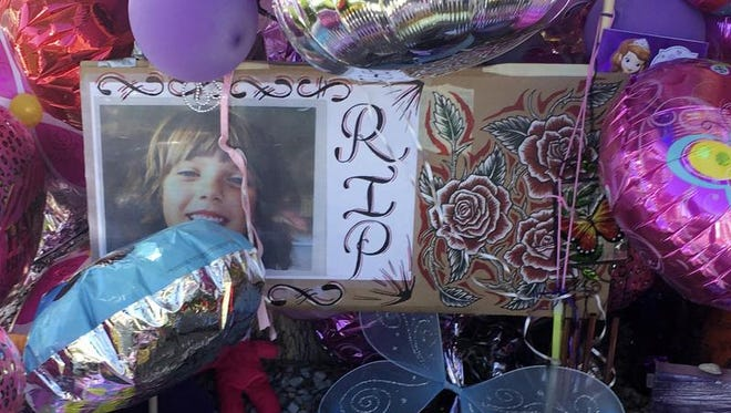 A picture of Victoria Martens, a 10-year-old Albuquerque girl brutally murdered, is placed in a memorial outside her former Albuquerque apartment on Monday, Aug. 29, 2016.