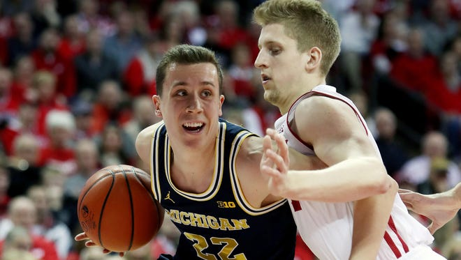 Michigan guard Duncan Robinson (22) drives the ball against Wisconsin guard Brevin Pritzl on Sunday, Feb. 11, 2018, in Madison, Wis.