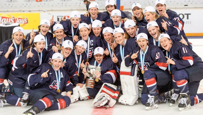 Team USA poses for a picture after defeating Canada, 1-0, in overtime to win the gold medal at the women's world hockey championships April 4, 2016, in Kamloops, British Columbia.