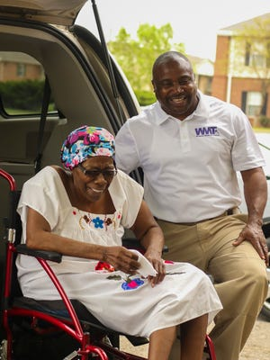 O'Neal Wiggins, founder of Wiggins Medical Transport, laughs with one of his clients, Helen Burton.