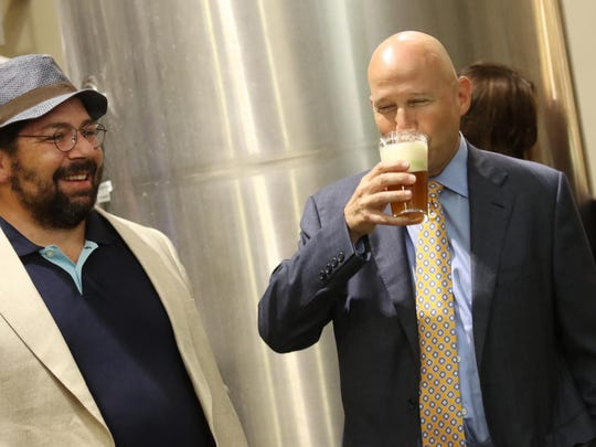 Co-owner J. Burke Morrison stands next to Gov. Jack Markell who took taste of a fresh beer from Twin Lakes Brewing Co. in Newport last Friday morning.